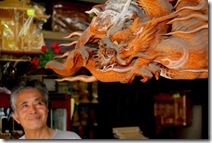 Masanobu Sonoda sob um releveode dragão em sua loja